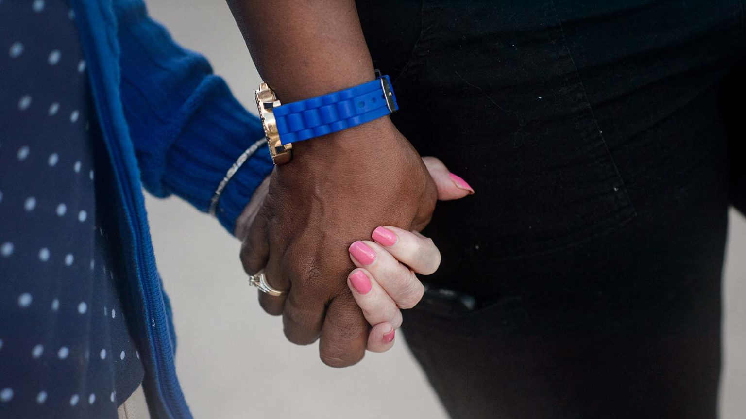 Staff member and senior woman holding hands walking
