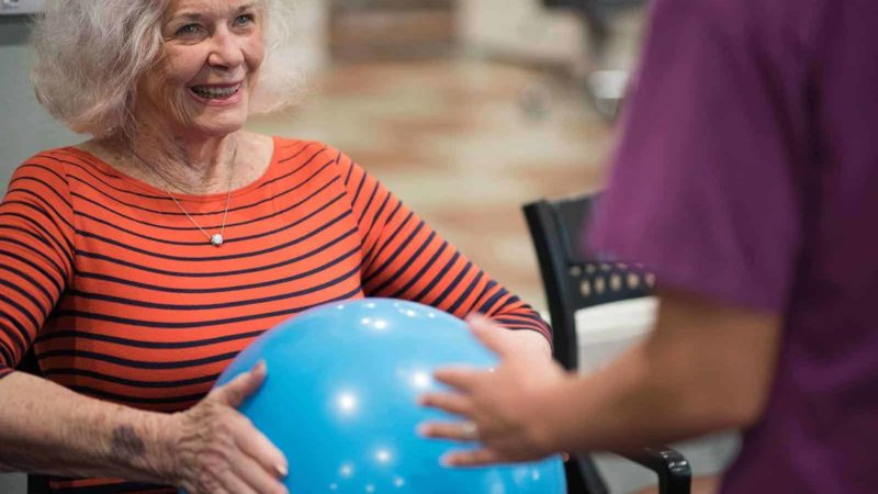 senior-woman-holding-rubber-ball-with-nurse-800x450
